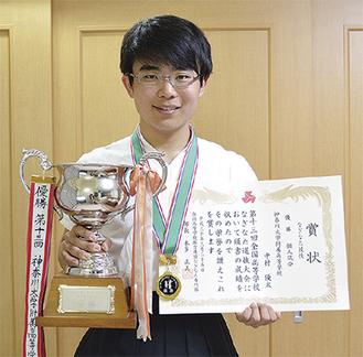 賞状とトロフィーを持つ中村さん