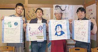 土のう袋を広げる塾スタッフと佐々木さん(右から2番目)