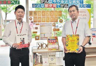 本棚の前に立つ佐久間局長(右)と石堂長津田北口郵便局長
