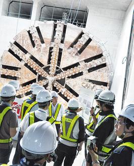 シールドマシンを前にトンネル内の説明を受ける報道陣
