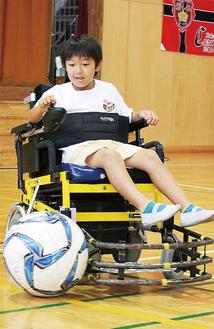 電動車椅子でシュートを放つ児童