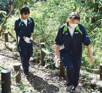 森の中から大きなごみを回収する東鴨居中生徒
