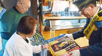 飲食店を訪問しポスターを手渡す阿部署長(右)
