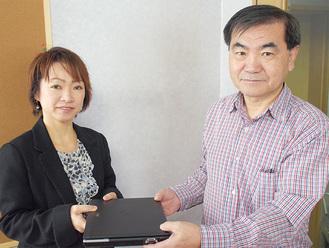 江成代表理事(左)にパソコンを手渡す清家代表