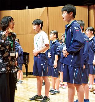根本氏(左)の指導で発声練習をする中学生