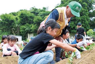 児童にコツを教える菅原会長(中央)