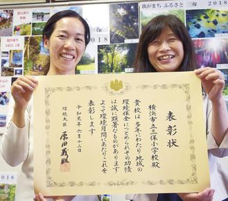 表彰状を手に笑顔を見せる安冨校長(右)と、新海教諭