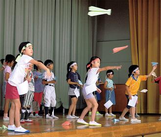 勢いよく紙飛行機を飛ばす児童