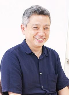 インタビューに笑顔で答える小川准教授