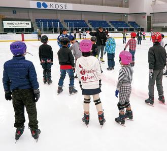 氷上で指導を受ける親子ら