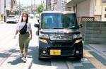 違法駐車の車両を避け車道を歩く女性(丸進不動産提供)