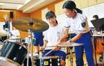 ドラムの叩き方を指導される場面