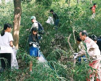 森の中でごみを拾う参加者