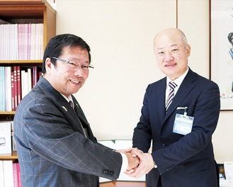 握手を交わす小野崎緑区長(右)と池田学長