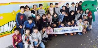 同小6年3組の児童とミドリン。完成した壁画左右約16m・天地約1.2m