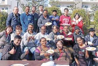 カレーを手に、笑顔のインド人、日本人の参加者たち