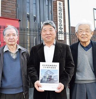 自治会館の前で完成した記念誌を手にする川崎会長(中央)と鈴木陽さん(右)、望月さん(左)