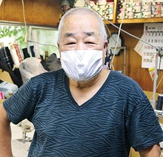 製作したマスクを付ける佐藤社長