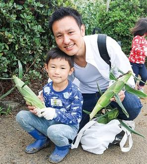 収穫したトウモロコシを持つ親子