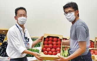 トマトを手渡す村田部長(右)