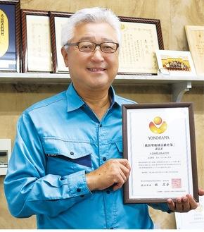 横浜型地域貢献企業の認定証を持つ土志田社長