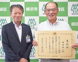 岡田区長(左)から手渡された表彰状を手にする塚田氏
