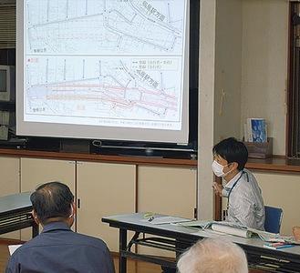 計画図面を見ながら地域住民に説明する市職員