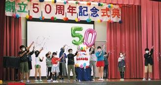 巨大なケーキを囲み、祝いのクラッカーを鳴らす児童ら