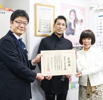 前田健康医療局長(左)から感謝状を受け取った矢幅さん(中央)と日下さん