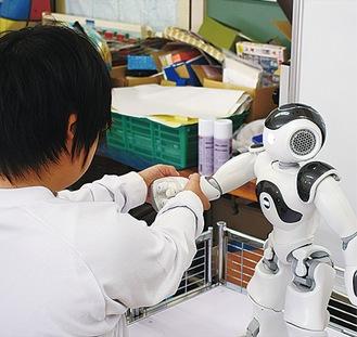 ロボットと握手をする生徒
