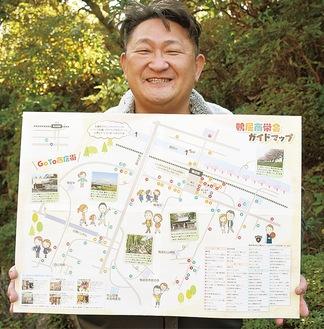 完成したガイドマップを手にする串田会長。ガイドマップは加盟店舗に置かれるほか、イルミネーション点灯式などで配布される