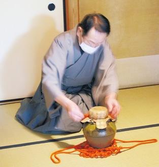 新茶の入った茶壷の封を切る金子さん