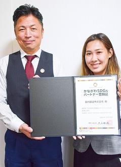 登録証と手にする佐藤総務部長(左)と同社社員