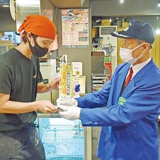 のぼり旗を渡す鈴木会長(右)