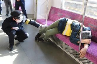 泥酔者への対応を確認する駅員(左)