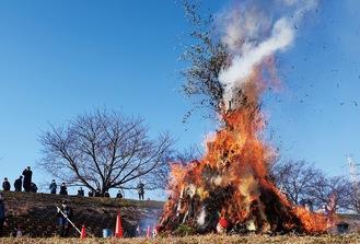燃え盛る炎を土手の上から見守る来場者