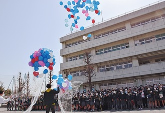 空へと飛び立つ風船を見上げる卒業生