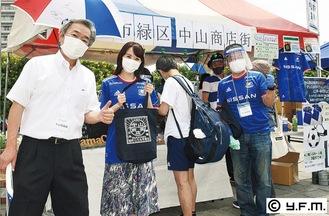 中山商店街ブースでPRするSakuさん(左から2人目)と、奥津理事長(左)