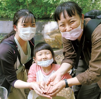 池からすくいあげたエビを手に乗せる大学生(左)と親子