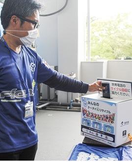 使用しなくなった携帯電話を試合会場に設置された回収箱に入れるファン