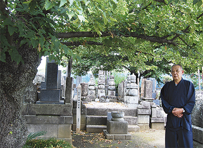 印融法印が眠る墓所前に立つ北田住職(右)