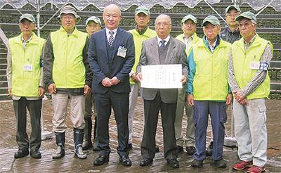 表彰状を手にする大川会長(中央右)と小野崎区長、会のメンバーら