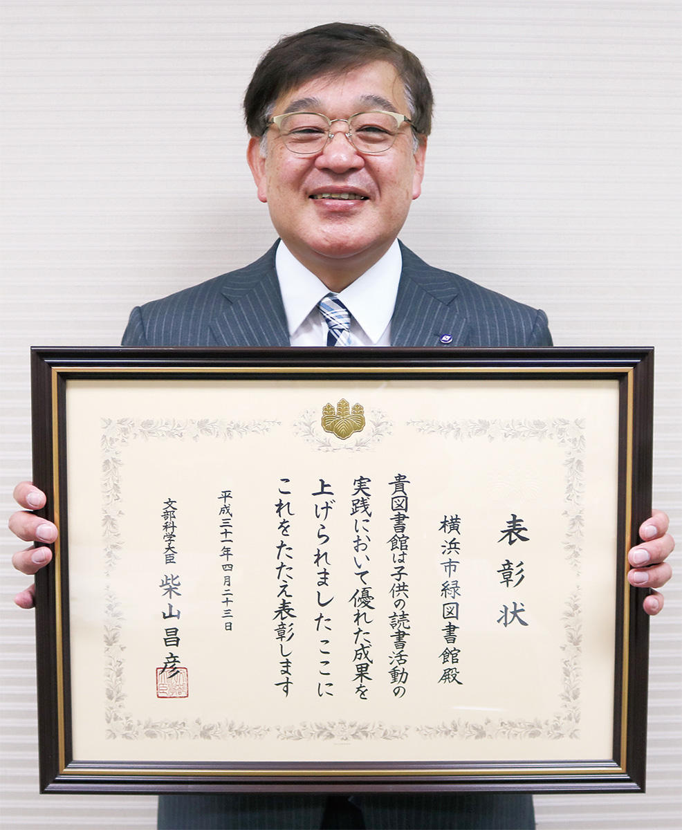 表彰状を持つ加藤緑図書館長