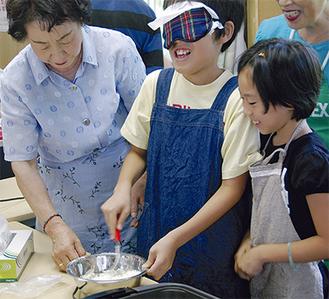 目隠しをして料理に挑戦する小学生ら
