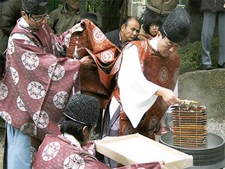 大釜から筒を引き上げる石川宮司