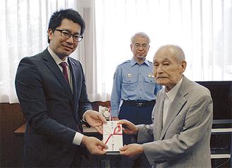 篠田店長(左)が嶋村代表理事に寄付金を贈呈