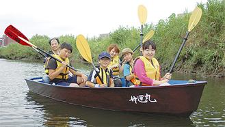 和舟「舟運丸」に乗る児童とスタッフ