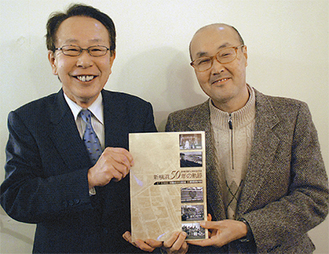 完成した記念誌を手に笑顔を見せる金子会長(左)と臼井さん