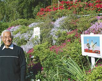 絵が展示された花壇で笑顔を見せる古田さん