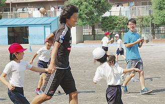 子どもたちと追いかけっこする中澤選手